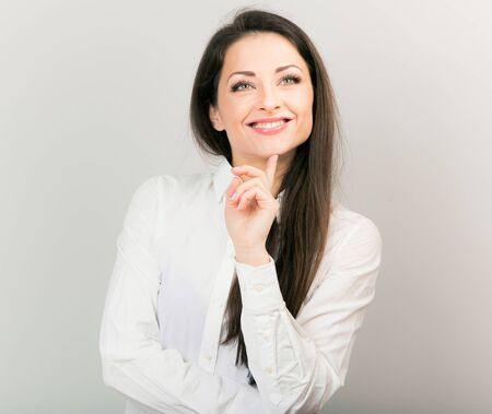 Beautiful positive business happy woman in white shirt showing idea sign by finger and looking up in white shirt and long hair.