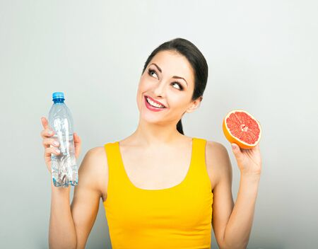 Happy smiling casual woman holding red grapefruit and water and thinking on blue background. Closeup portrait. Proper nutrition Banco de Imagens