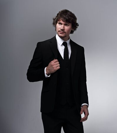 Business man in black fashion suit posing on gray bacground with serious face and folded arms. Closeup studio portrait Zdjęcie Seryjne
