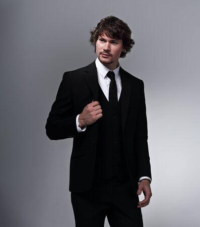 Hombre de negocios en traje negro posando en fundamento gris con rostro serio y brazos cruzados. Retrato de estudio de primer plano Foto de archivo
