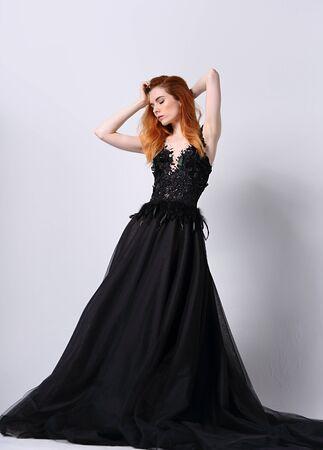 Belle jeune mannequin élégante avec une coiffure foxy lumineuse posant dans une robe noire chic à la mode avec une jupe longue sur fond gris studio Banque d'images