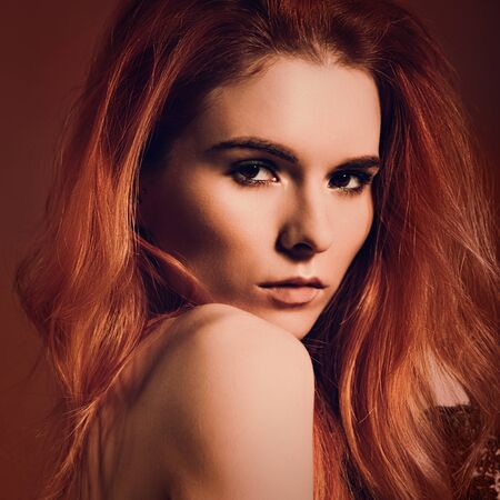 Beautiful passion look young woman with volume red hair style on orange dark studio background. Closeup bright portrait. Toned bright color Standard-Bild