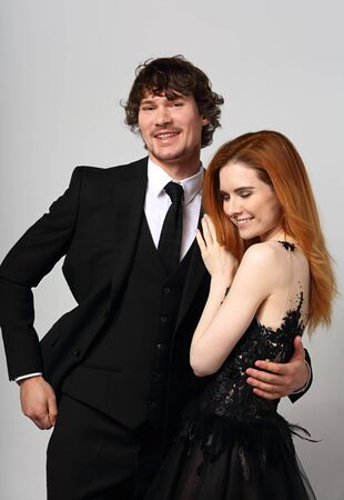 Beautiful happy couple hugging on blue background in evening fashion clothing. Redheaded hairstyle laughing girl and brunette man in studio. Closeup portrait