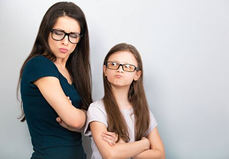 Resentful thinking mother and injured kid in glasses with folded arms on light blue background.
