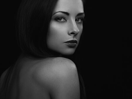 Beautiful mystic woman with long hair with secret in look of chic eyes on black background with empty copy space. Closeup portrait. Art.Expression portrait. Vogue. Black and white