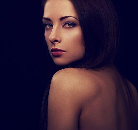 Beautiful makeup mystic woman with long hair with wild look on black background with empty copy space. Closeup portrait. Art.Expression portrait. Vogue. Toned color portrait