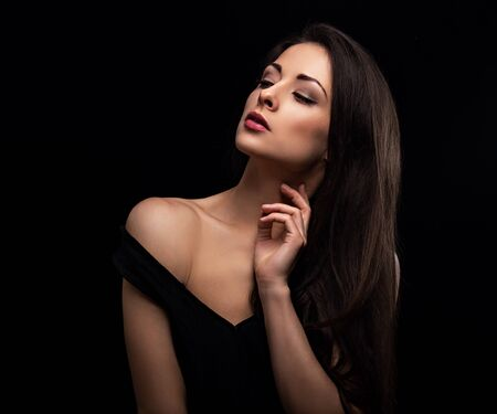 Beautiful makeup sexy woman with long hair looking sensual with elegant hand and fingers near the neck on black background. Closeup portrait. Art.Expression portrait. Vogue.