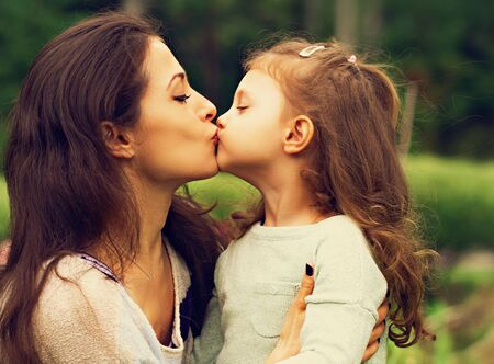 Beautiful mother and cute small daughter kissing in lips on summer green background. Closeup family portrait