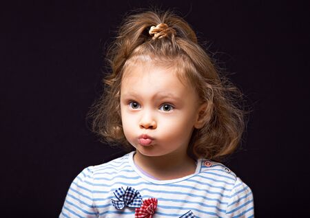 Excited surprising small kid girl looking fun with big eyes and grimacing face and pouted lips on black studio background. Closeup portrait