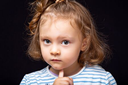 Cute small concentrated kid girl with serious face looking and decided the question on black studio background. Closeup portrait