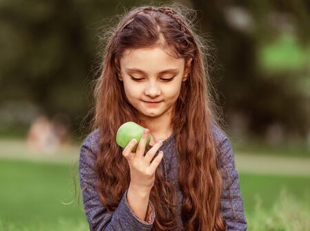 Beautiful long hair fun kid girl enjoying and eating green apple on summer grass background. Closeup pastel color portrait Banque d'images