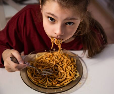 Grimacing kid girl eating tasty spaghetti on the dinner and looking up her curious ungry big eyes at the home kitchen. Closeup funny portrait