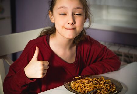 Pretty grimacing kid girl eating tasty spaghetti on the dinner on the home kitchen and showing thumb up sigh. Closeup funny portrait