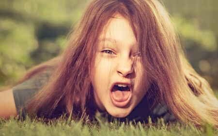 Crazy angry kid girl shouting with opened mouth and mad hair lying on the green grass on outdoor summer background. Closeup emotional portrait of difficult child. Vintage