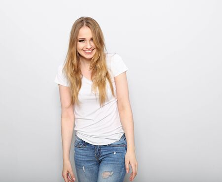 Pretty toothy laughing young woman with fair blond long hair in casual dress, blue jeans and t-shirt. Studio shot of good looking beautiful woman isolated against grey studio wall with empty space