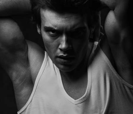 Sexy male model posing in white underwear in dark shadow background with angry emotional look. Closeup portrait of strong muscular handsome man