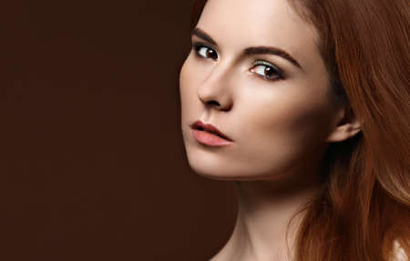 Beauty makeup woman with red volume hair style and wide brow. Closeup portrait on orange background with empty copy space