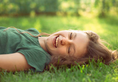 Happy laughing fun casual kid girl lying on the grass on nature summer background. Closeup positive outdoors portrait