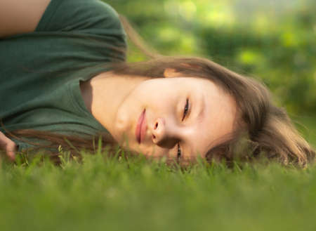 Happy smiling calm casual kid girl lying on the grass on nature summer background. Closeup positive outdoors portrait