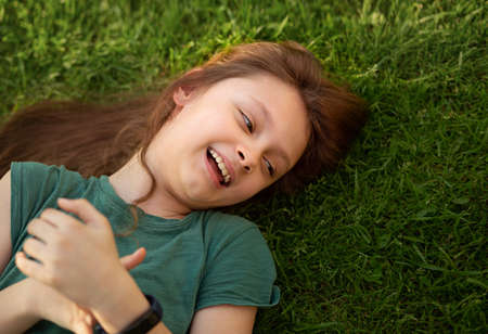 Laughing playful kid girl lying on the grass on nature summer background. Closeup positive outdoors bright sunny portrait Stok Fotoğraf