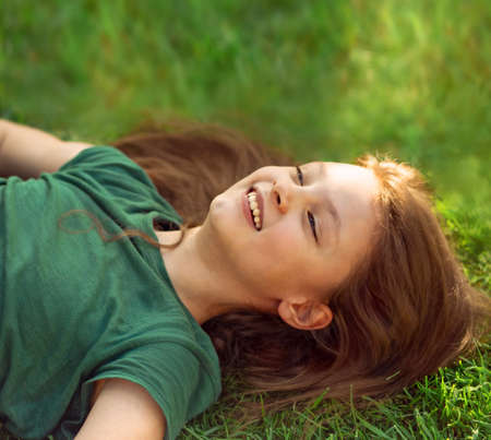 Laughing playful kid girl lying on the grass on nature summer background and looking up. Closeup positive outdoors bright sunny portrait Stok Fotoğraf