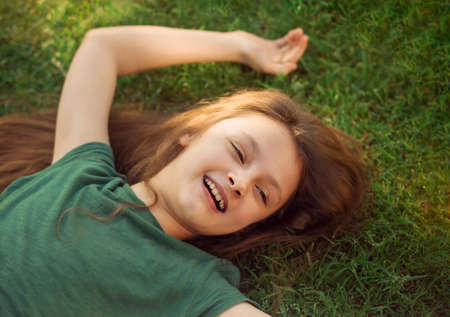 Happy laughing relaxing kid girl lying on the grass on nature summer background. Closeup positive outdoors bright sunny portrait Stok Fotoğraf