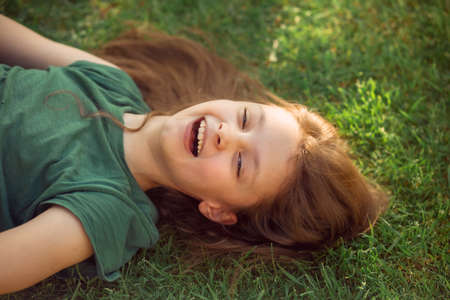 Happy laughing fun kid girl lying on the grass on nature summer background. Closeup positive outdoors bright sunny portrait Stok Fotoğraf