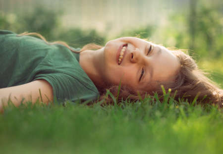 Happy smiling relaxing casual kid girl lying on the grass on nature summer background. Closeup positive outdoors portrait
