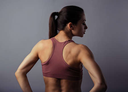 Sporty strong healthy body young woman posing in sport top on violet background with empty copy space. Closeup portrait. Back view. The concept of medicine, massage, physiotherapy.