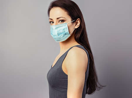 Female in respiratory blue mask. Masked serious woman looking on camera. Cold, flu, virus, tonsillitis, respiratory disease, quarantine, epidemic concept portrait. Beautiful caucasian young woman in disposable face mask. Closeup