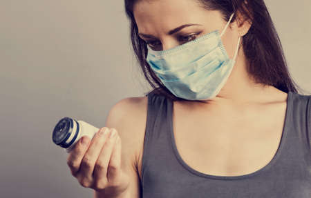 Female in respiratory blue mask. Masked serious woman holding medical tablet in the hand. Cold, flu, virus, tonsillitis, respiratory disease, quarantine, epidemic concep. Caucasian young woman in disposable face mask.Closeup