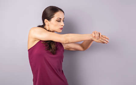 Young sporty woman stretching the arms, shoulder in sport wear clothing on purple background with empty copy space. Closeup healthy lifestyle portrait