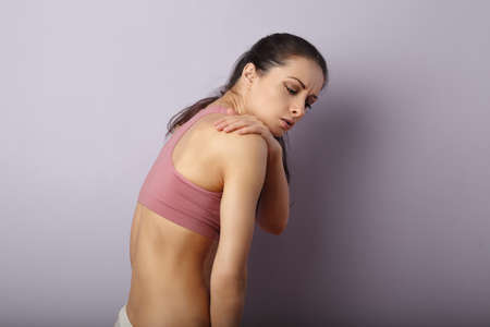 Young unhappy woman suffering from shoulder pain. clothing on sporty short top. Touching and massaging the hands. Sports exercising injury. Closeup portrait on purple background with empty copy space. Back view Stok Fotoğraf
