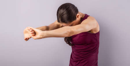 Young sporty woman stretching the arms, shoulder and back in sport wear clothing on purple background with empty copy space. Closeup healthy lifestyle portrait 스톡 콘텐츠
