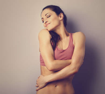 Happy strong sporty woman in sport wear with love hugging herself with natural emotional smiling face on purple background. Closeup vintage portrait Stok Fotoğraf