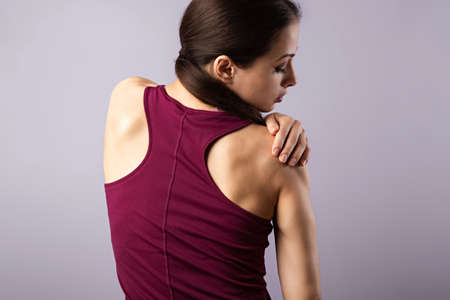Young strong sporty woman looking on the shoulder with pain. Touching and massaging the hands. Sports exercising injury. Closeup portrait on purple background with empty copy space. Back view