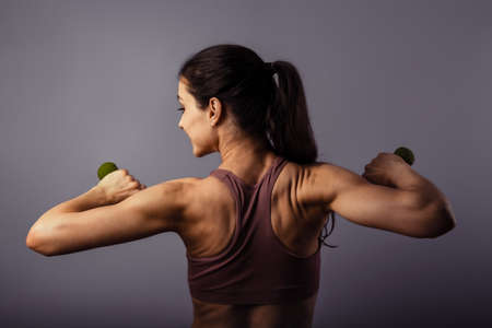 Sporty strong healthy happy woman training with dumbbells in hands in sport top on violet background. Closeup portrait. Back view. The concept of health life