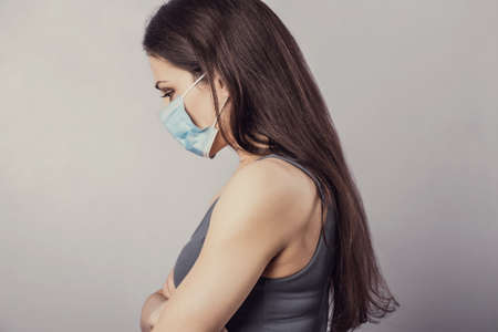 Female in respiratory blue mask. Serious woman looking down. Cold, flu, virus, tonsillitis, respiratory disease, quarantine, epidemic concept portrait. Beautiful caucasian woman with empty space. Closeup Stok Fotoğraf