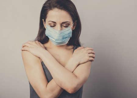Beautiful sad woman hugging herself the arms with love in respiratory mask. Cold, flu, virus, tonsillitis, respiratory disease, quarantine concept portrait. Beautiful caucasian woman supporting yourself. Closeup toned