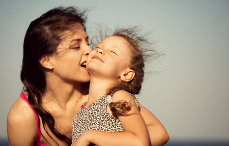 Happy beautiful playul mother hugging and humor biting her enjoying fun kid girl on vacation sea summer holidays. Closeup outdoor natural family portrait Stok Fotoğraf