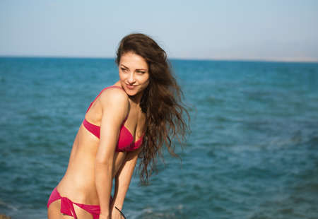 Beautiful sexy body woman in pink bikini swimming in the sea with enjoying face on the blue sky summer background. Healthy face skin and long windy hair. Closeup holidays portrait