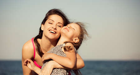 Happy beautiful mother hugging and laughting her playful enjoying kid girl on vacation sea summer holidays. Closeup outdoor natural family portrait