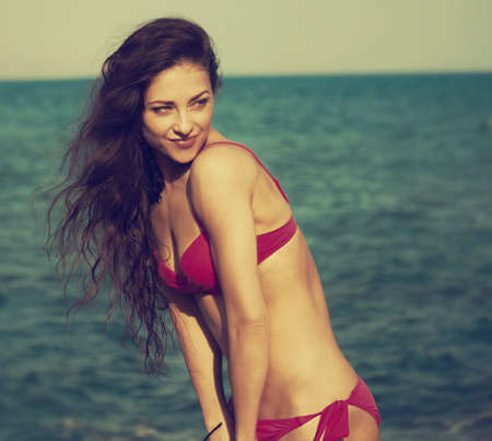 Beautiful sexy body woman in pink bikini swimming in the sea with enjoying face on the blue sky summer background. Healthy face skin and long windy hair. Closeup holidays portrait. Toned vintage color Stok Fotoğraf
