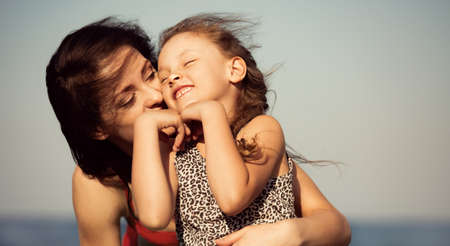 Happy beautiful mother hugging her playful enjoying kid girl on vacation sea summer holidays. Closeup outdoor natural family portrait
