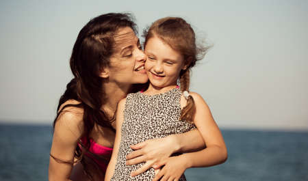 Happy beautiful mother hugging and kissing her playful enjoying kid girl on vacation sea summer holidays. Closeup outdoor natural family portrait Stok Fotoğraf