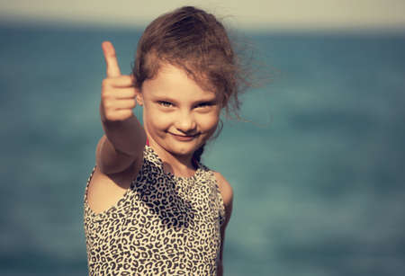 Small kid girl relaxing and gesturing the hand success thumb up sign on blue sea background. Closeup holidays portrait Stok Fotoğraf