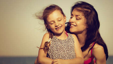 Happy beautiful mother hugging her playful laughing kid girl on vacation sea summer holidays. Closeup outdoor natural family portrait. Vintage bright color portrait Stok Fotoğraf