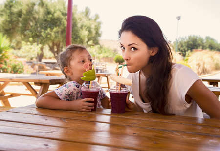 Happy kid girl and grimacing emotional mother drinking berries smoothie juice together in street summer cafe. Closeup portrait