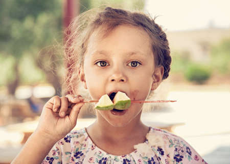 Fun cute thinking kid girl eating the pieces of cut apples with serious beautiful big opened eyes in summer cafe. Closeup portrait