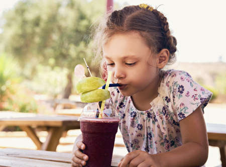 Fun cute thinking kid girl drinking smoothie juice with serious look in summer cafe. Closeup vacation portrait